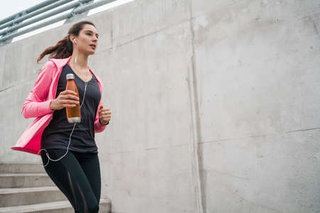 Portrait of a sport woman running on stairs outdoors. Fitness, sport and healthy lifestyle concepts. Reklamní fotografie