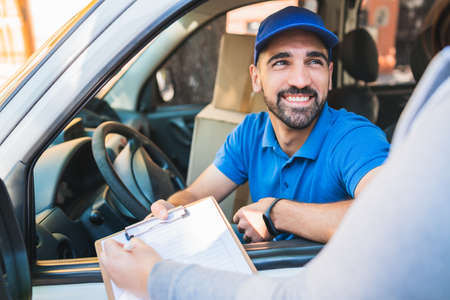 Delivery man in van while customer sign in clipboard.