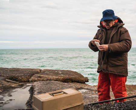 Fisherman with fishing equipment box.