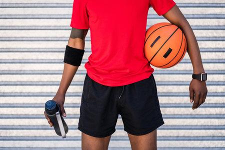 Afro athlete man holding a basketball ball outdoors. Standard-Bild