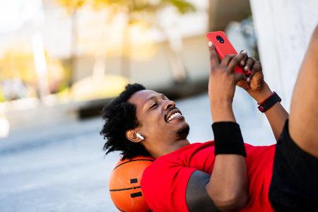 Athlete man using his mobile phone.