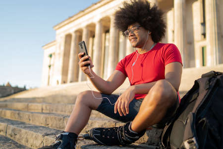 Latin man using mobile phone outdoors.