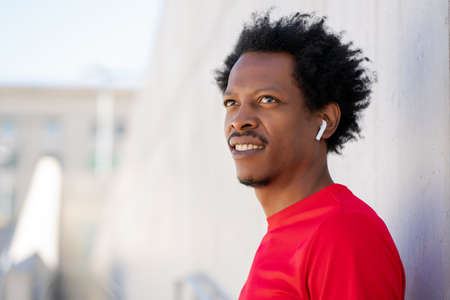 Afro athletic man standing outdoors.