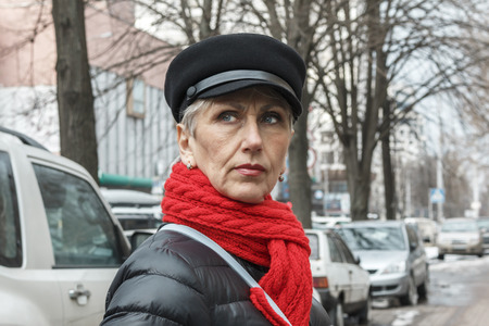 pretty and serious middle-aged lady in a red scarf, cap, earrings and black jacket against the background of the city. closeup portrait of elegant middle aged woman. Lovely middle-aged gray-haired woman with a serious face. serious middle-aged woman with wrinkles on face and red scarf