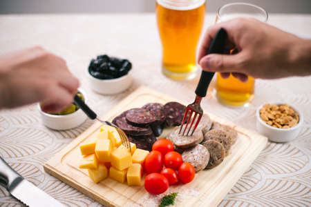 Chopped on a wooden board with codeguín, cheeses, Basque blood sausage, olives and beers