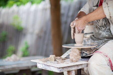 alfarero: alfarero produce la copa en un torno de alfarero Foto de archivo