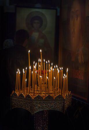 arrepentimiento: la quema de velas delante de los iconos en el templo Foto de archivo