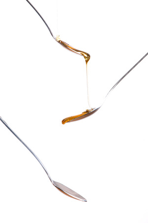 freisteller: Honey on spoon with on a white background