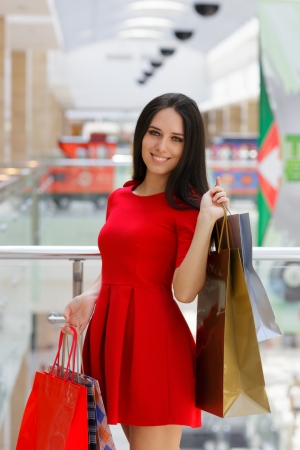 red centre: Young Woman Shopping in Mal with Shopping Bags Stock Photo