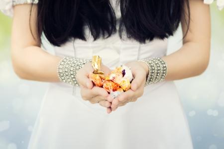 generosity: Manos de la muchacha s la celebración de dulces Foto de archivo