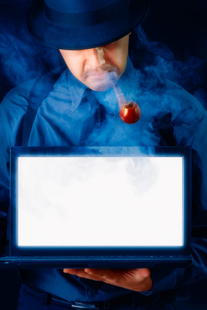 Man with Hat and Pipe Holding Laptop with White Screen photo