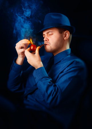 Man with Hat Lighting His Pipe with a Match photo
