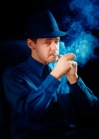 Man with Hat Lighting His Pipe  photo