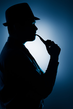 Silhouette of Man Smoking Pipe on a Spotlight Background  photo
