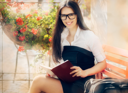 Young Woman with a Book Sitting on a Bench photo