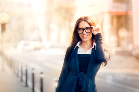 都市の外のガラスを持つ若い女