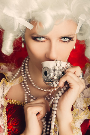 Beautiful Baroque Woman Portrait Drinking from a Cup  photo