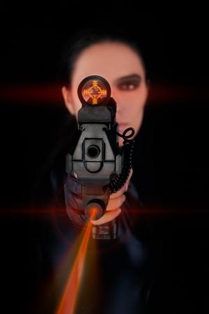 mujer con pistola: Esp�a de la mujer que apunta el arma con mira l�ser Foto de archivo