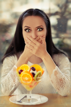 unpleasant: Surprised Young Woman with Fruit Salad Dessert