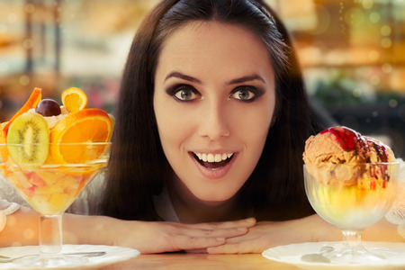 tempting: Young Woman Choosing Between Fruit Salad and Ice Cream Desserts  Stock Photo
