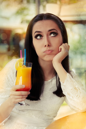 Bored Woman with Colorful Cocktail Drink photo