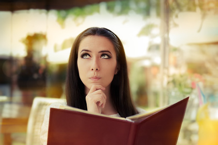 ordering: Young Woman Choosing from a Restaurant Menu  Stock Photo