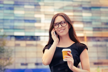 Young Woman with Coffee Cup on the Phone Out in the City  photo