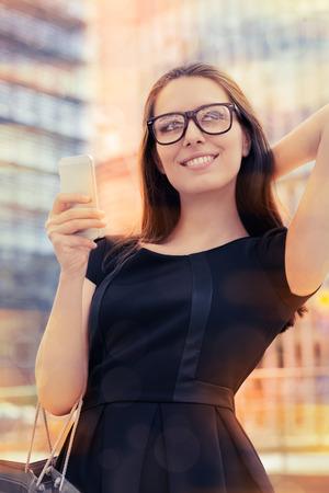 ショッピング バッグや都市の外の電話を持つ若い女性