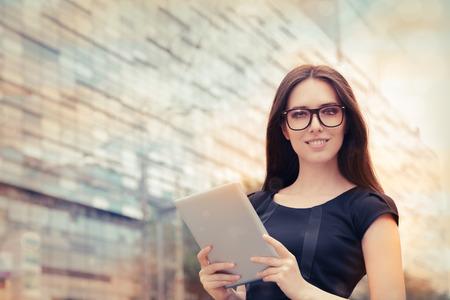 都市の外のタブレットを持つ若い女性