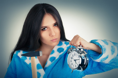 Young Woman Holding a Hammer and an Alarm Clock  photo