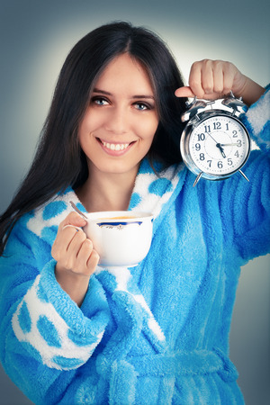 Young Woman in Bathrobe Holding an Alarm Clock and a Cup of Coffee   photo