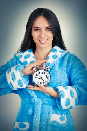 Young Woman in Bathrobe Holding an Alarm Clock  photo