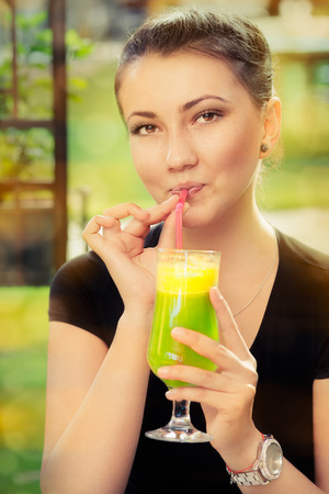 Young Woman with Colorful Cocktail Drink Outside  photo