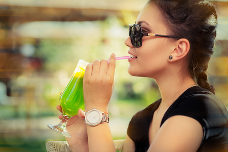 Young Woman with Sunglasses and Colorful Cocktail Drink Outside  photo