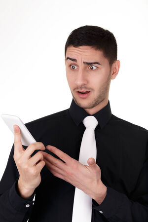 Young Businessman Looking Surprised at His Smart Phone Stock Photo