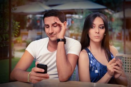 Pareja secreta con los teléfonos inteligentes en sus manos Foto de archivo - 31627422
