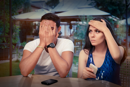 mistake: Young Couple Having Problems with Their Smart Phones  Stock Photo
