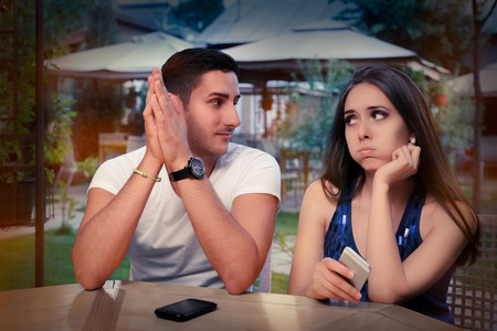moody: Young Couple Having Problems with Their Smart Phones  Stock Photo