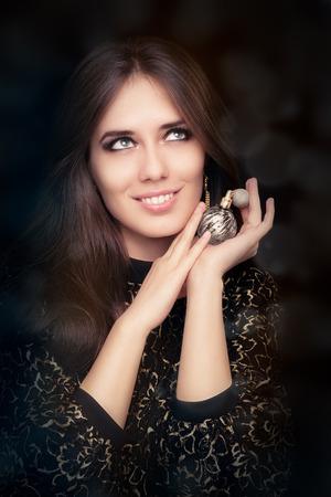 perfume bottle: Retro glamour woman holding vintage perfume bottle