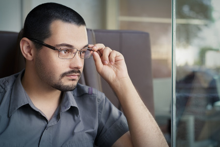 vigilant: Portrait of a young man wearing glasses looking out of a window