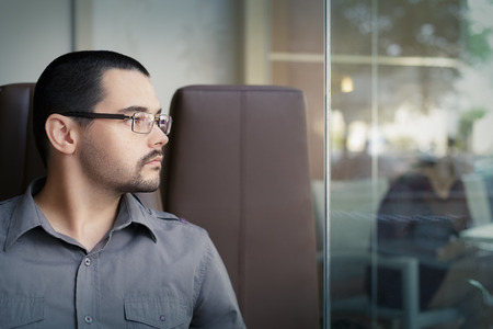Portrait of a young man wearing glasses looking out of a window photo