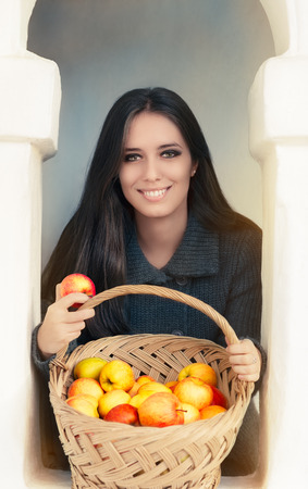 Portrait of a woman holding a basket full of organic apples photo