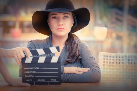 幅の広い帽子を身に着けている若い女性は、新しいシーンを撮影する準備ができて