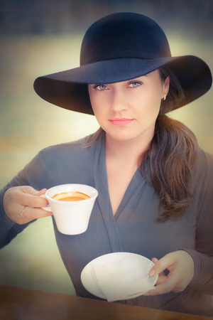 Young woman wearing a broad hat is out for a cup coffee photo