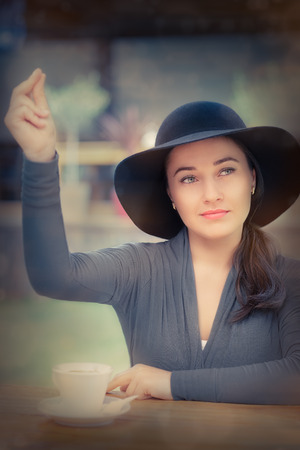 Young woman wearing a broad hat snaps her fingers to call the waiting staff photo