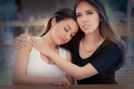 Young woman consoling her best friend photo