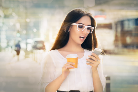 buss: Shocked woman looking at her phone  holding a cup of coffee out in the city
