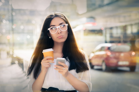 Expressive woman holding phone and cup of coffee out in the city photo