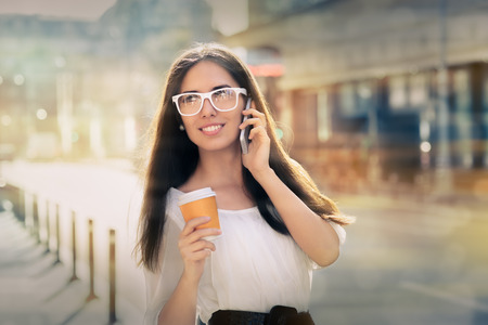 answering call: Woman smiling and talking on her phone holding a cup of coffee out in the city