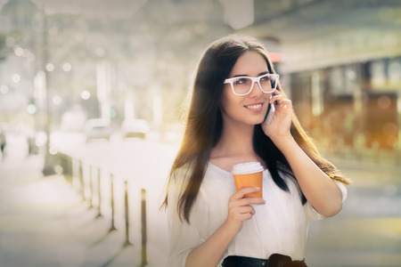 Woman smiling and talking on her phone holding a cup of coffee out in the city